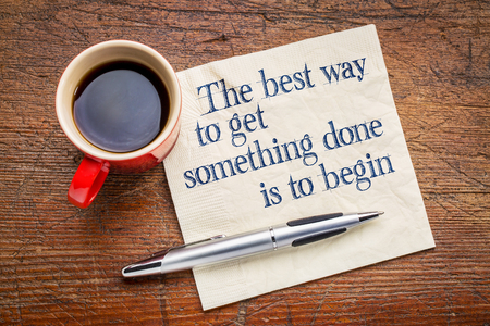 complete solution: the best way to get something done is to begin - inspirational phrase on a napkin with cup of coffee