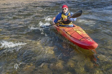 paddler: senior male paddler is paddling whitewater kayak on a turbulent river Stock Photo