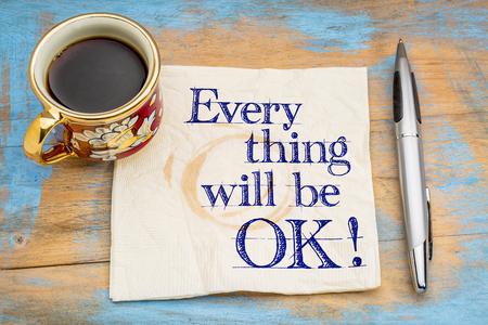 attitudes: Everything will be OK! Handwriting on a napkin with a cup of coffee and pen.