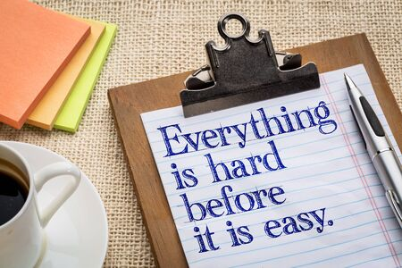 Everything is hard before it is easy - motivational slogan on a clipboard with a cup of coffee Stock Photo