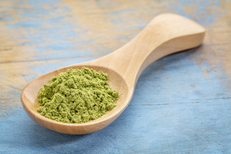 moringa leaf  powder on wooden spoon against blue painted grunge wood