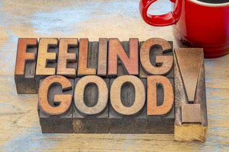 feelings of happiness: feeling good - words in vintage letterpress wood type printing blocks stained by color inks with a cup of coffee