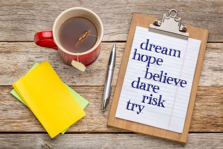 Dream, hope, believe, dare, risk and try - inspirational words on clipboard  with a pen, tea and sticky notes against rust wood table- office concept