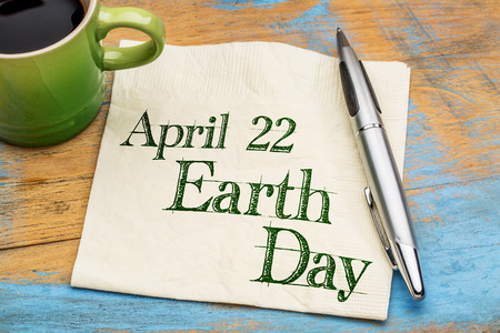 earth day: April 22 Earth Day reminder - handwriting on a napkin with cup of coffee Stock Photo