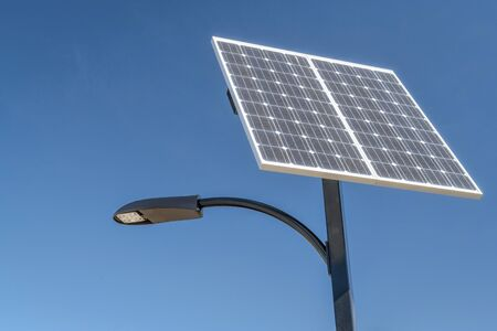 street lamp with a solar panel against blue sky Stockfoto