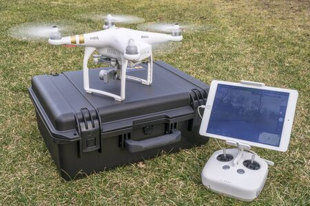 phantom: Fort Collins, CO, USA - March 12, 2016:  DJI Phantom 3 quadcopter drone is taking off from a pelican case with radio controler and iPad in foreground