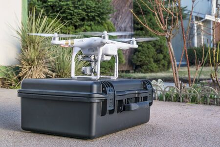 phantom: Fort Collins, CO, USA - March 10, 2016:  DJI Phantom 3 quadcopter drone is taking off in a house driveway - application of drone technology in real estate photography.