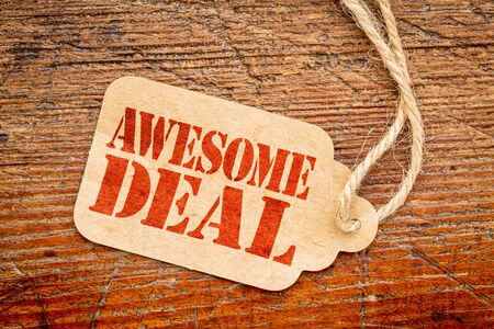 awesome deal sign - red stencil text on a paper price tag against grunge wood