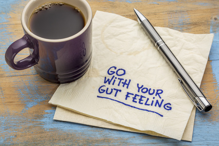 intuition: go with your gut feeling - advice or motivational reminder  on a napkin with cup of espresso coffee