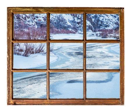 sash: Frozen mountain river as seen  through vintage, grunge, sash window with dirty glass Stock Photo