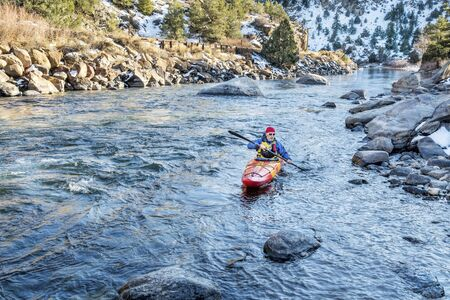 upstream: senior kayaker in a whitewater kayak paddling upstream of Arkansas River above Hecla Junction, Colorado in winter scenery Stock Photo