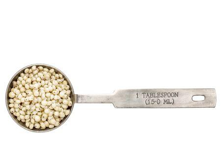 sorgo: gluten libre de grano de sorgo en una cucharada de medición de metal aislado en blanco