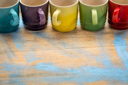 stoneware: a row of empty colorful stoneware coffee cups  against grunge painted wood with a copy space