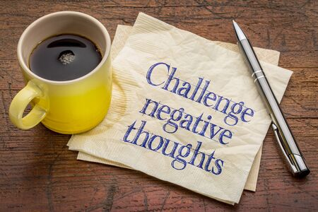 challenge negative thoughts - inspirational advice or reminder - handwriting on a napkin with a cup of coffee Banco de Imagens