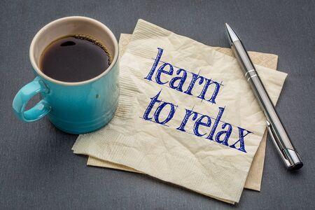 アドバイスやリマインダー - 灰色スレート石の背景のコーヒーのカップでナプキンに手書きでリラックスすることを学ぶ