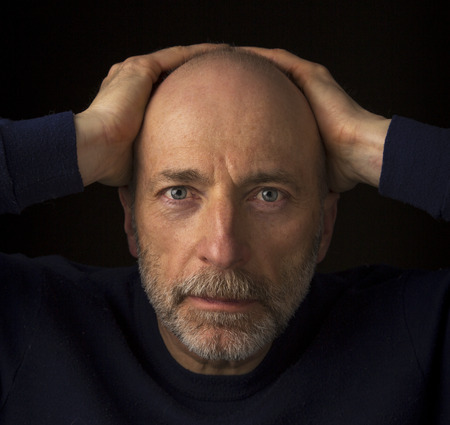 60 years old: 60 years old  bald man with a beard - a headshot against a black background Stock Photo