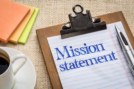 mission: mission statement - handwriting on a clipboard with a cup of coffee