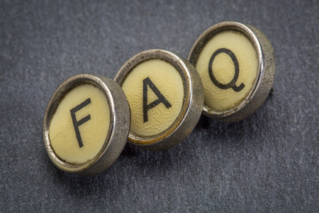 frequently: FAQ (frequently asked questions) acronym in old round typewriter keys against gray slate stone