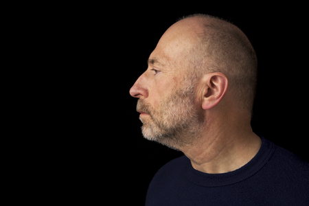 60 years old: 60 years old  bald man with a beard - a profile headshot against a black background