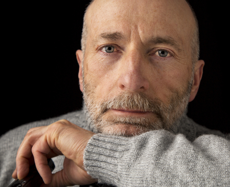 60 years old: confident and positive 60 years old man with a beard - a headshot against a black background