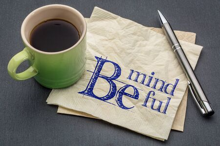 mindful: Be mindful  - handwriting on a napkin with cup of coffee against gray slate stone background Stock Photo