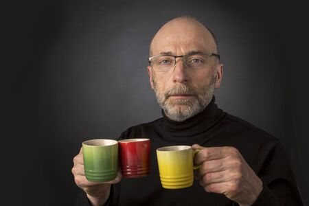 glass cup: Morning coffee anybody? 60 years old  bald man with a beard and glasses carrying three espresso coffee cups - a headshot against a black background Stock Photo