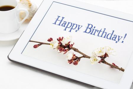 flores de cumpleaños: tarjeta de felicitación del feliz cumpleaños - escritura a mano con las flores del albaricoque sobre tableta digital con una taza de café