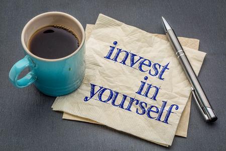 教育: アドバイスやリマインダー - 灰色スレート石の背景のコーヒーのカップとナプキンの手書きの文字は、自分自身に投資します。