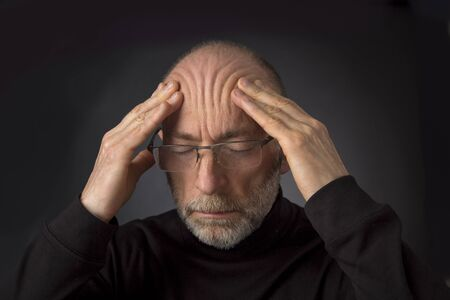 60 years old: tired - 60 years old  man with a beard and glasses massaging his forehead -  a headshot against a black background Stock Photo
