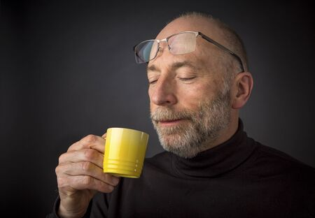 60 years old: Enjoying morning espresso coffee - 60 years old  man with a beard and glasses - a headshot against a black background