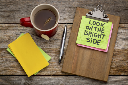 Look on the bright side advice or reminder - sticky note on a clipboard with a cup of tea