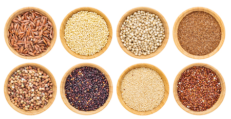 gluten free grains collection  - buckwheat, amaranth, brown rice, millet, sorghum, teff, black and red quinoa - top view of isolated wooden bowls