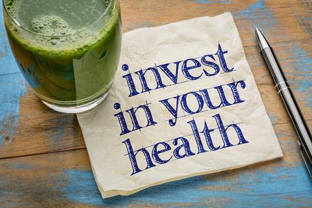 gezondheid: investeren in uw gezondheid advies of herinnering - handschrift op een servet met een glas vers, groen, groentesap Stockfoto