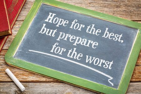 prepare: Hope for the best but prepare for the worst - advice on a slate blackboard with a white chalk and a stack of books against rustic wooden table