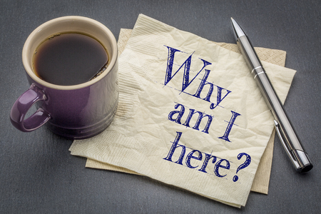 i am here: Why am I here question  - handwriting on a napkin with cup of coffee against gray slate stone background