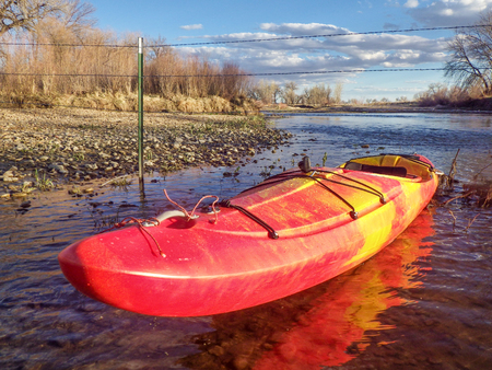 barbed wire fence: kayak and barbed wire  fence across river - St Vrain Creek below Longmont in Colorado