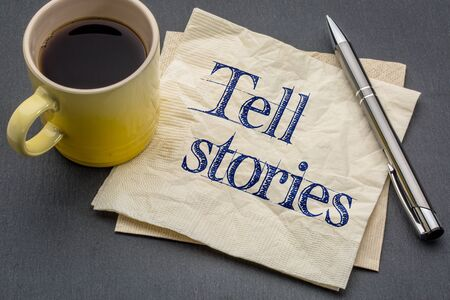 anecdote: Tell stories advice or reminder - handwriting on a napkin with cup of coffee against gray slate stone background