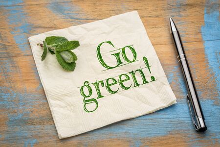 Go green message or  encouragement on napkin with a fresh peppermint leaf