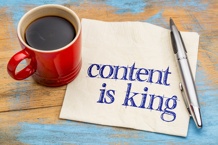 content is king - writing, blogging and publishing concept - handwriting on a napkin with a cup of coffee Foto de archivo