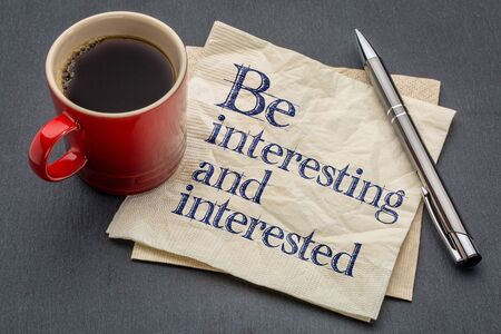 Be interesting and interested advice or reminder - handwriting on a napkin with cup of coffee against gray slate stone background