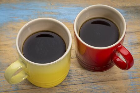 stoneware: two stoneware cups of espresso coffee against grunge painted wood