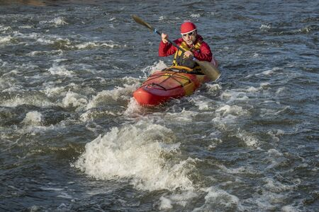 upstream: whitewater kayaker paddling upstream the river rapid Stock Photo