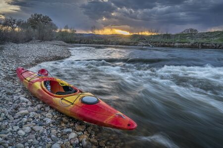 whitewater kayak and river rapid at sunset - Cache la Poudre River in Fort Collins, Colorado Stock Photo