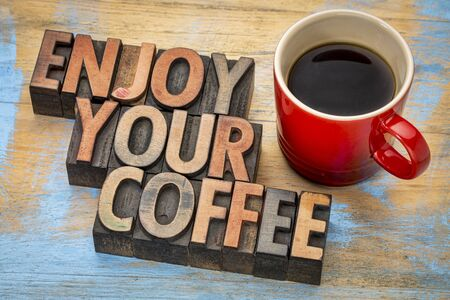 wood type: enjoy your coffee  - text in vintage letterpress wood type printing blocks with a cup of espresso coffee