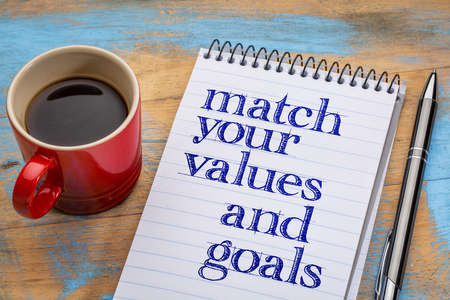 morale: Match your values and goals - inspirational advice or reminder in a spiral notebook with a cup of coffee Stock Photo