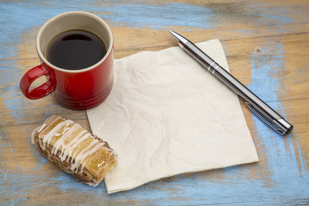 blank napkin with a pen,cup of espresso coffee and cookie against grunge painted wood