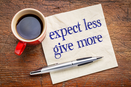 self improvement: expect less, give more advice - motivation or self improvement concept - handwriting on a napkin with a cup of coffee