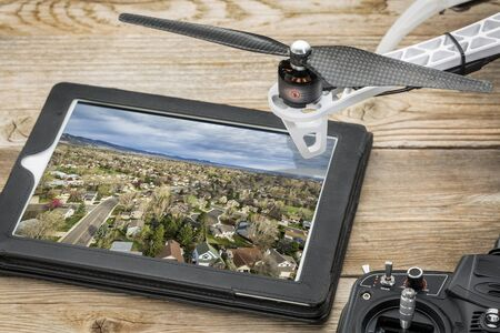 drone aerial photography concept - reviewing aerial picture of residential area on a digital tablet with a drone rotor and radio control transmitter, Imagens