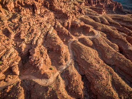 4wd: aerial view of a windy 4WD road through red sandstone canyon with coarse vegetation near Moab, Utah