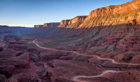 moab: aerial view of a windy road through red sandstone canyon with coarse vegetation near Moab, Utah